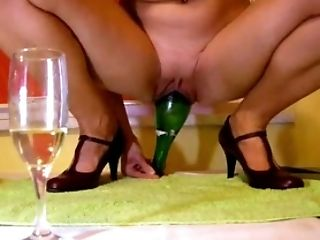 Filthy mature woman stretching her vagina with a glass bottle